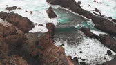 vista de cima : Beautiful bay created from cliffs of frozen lava, a beach with volcanic sand and the Atlantic Ocean. Aerial view of a natural pool Stock Footage