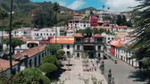 routes : Aerial view - drone flies over a small colorful Spanish city located in the mountains. Colorful houses of ancient architecture on a sunny day. Teror, Gran Canaria, Spain.