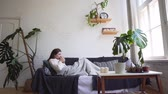 pullover : A young woman on the couch enjoys relaxing - drinks a hot drink, wraps herself in a blanket and lies on pillows. Cosiness and comfort during the winter holidays Vidéos Libres De Droits