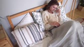 pullover : Coziness, happiness and comfort in the bedroom - the girl in bed reads a book and rests after a hard day on a cold day Vidéos Libres De Droits