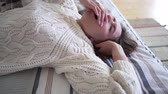 roupa de dormir : Rest time after a hard days work - Caucasian girl in a beautiful comfortable white sweater knitted from wool regains strength on the bed Vídeos
