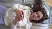 detection : Concept of comfort - shopping at home using the phone. A woman buys products, lying in a cozy bedroom, at home.