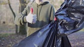 сохранение : A female volunteer shows like and a black garbage bag, after clearing the forest of plastic. Environmental issues
