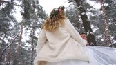 trees : Woman in long dress and silver shoes walking at winter sunny day in slow motion Stock Footage