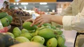 raflar : Womans hands choosing the fresh mangoes in the supermarket