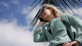 circling : Happy caucasian woman with long blonde hair in sunglasses and green shirt standing and talking on phone near palm tree on a blue sky background. Travel concept
