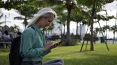 uzun saçlı : Beautiful slim woman with long blonde hair in green shirt sits on the ground and using smartphone over background the park. Girl on the square touching screen and smile. Stok Video