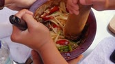 モルタル : Thai womens preparing green papaya salad som tam in wooden mortar with pestle. Close Up. 4k
