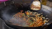 rice pan : Cook fries noodles in a wok with shrimps and vegetables at a street market. 4k