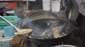 Cook fries rice in a wok with vegetables at a street local market. 4k Dostupné videozáznamy