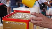 The seller pours iced tea in the local market. Closeup. 4k