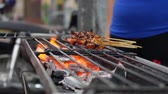 Сингапур : Traditional grilled meat on sticks cooked at street local market. Satay bbq. Closeup. 4k