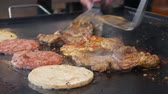 Cooking burger. Beef or pork big, lush, delicious cutlets from different types of meat grilling on the pan. Closeup. 4k