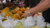 ananas : A woman chooses and buys guava on the Asian street market. 4k