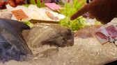 barbatana : Customer choose and buy Black Pomfret fish in asian street market. Fresh in ice ready for sell. Closeup. 4k