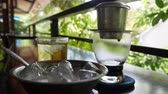 maker : Brewing black coffee using a Vietnamese Traditional phin Filter in cafe. Coffee drips slowly drops in a glass cup. Ca phe den da. Closeup. 4k