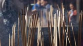 blessed : People praying and worshipping in Taoist temple interior bowing and holding incense sticks during the celebration of Chinese New Year. The big outdoor pot with incenses, fulfilled with sand, is staying on the table. Close-up. 4k Stock Footage