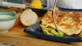 dobrado : Someone eats omelet with vegetables, salad and avocado in restaurant. Scrambled eggs on a plate. Yummy. Close-Up