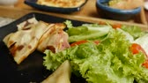 koekenpan : Pancakes with ham and cheese on a black plate with salad in a restaurant. Breakfast time. Close-up