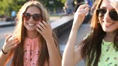 slomo : Two pretty beautiful fashionable girls are laughing outdoors
