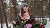 ringed : Portrait of beautiful mixed race caucasial asian girl holding a bouquet of flowers in winter snowy pine forest during snowfall and waiting for groom and first meet. Valentines Day concept.