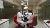 folder : 6 June, 2014, Donetsk, Ukraine, Elements Dental. Health and dental care, female dentist and her assistant nurse at work at modern office with client. Complicated dental surgery.