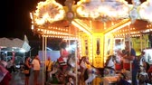 eğlence peşinde : Children enjoy Merry Go Round ride with their parents Stok Video
