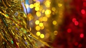 Christmas and New Year holiday celebration. Gold Christmas tinsel garland decorations blowing in the breeze. Blurred Christmas lights blinking in the background. Стоковые видеозаписи