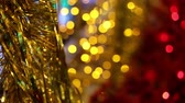 Christmas and New Year holiday celebration. Gold Christmas tinsel garland decorations blowing in the breeze. Blurred Christmas lights blinking in the background. Filmati Stock