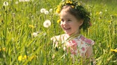 humane : A little girl sitting in a meadow blows into a dandelion and has fun