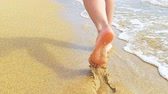 Beautiful woman legs, runn along the sand beach. Walking in the water.