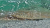 Waves crashing on stones in sea. Slowmotion close-up
