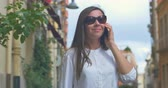 gossip : Woman talking on cellphone in the old european city, steadicam shot