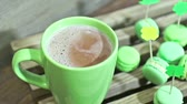 Green cup of the hot chocolate and green macaroons with St Patricks Day attributes over focus. Slow motion.