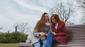 Female teenagers discussing a book sitting on the bench in an autumn city park Stock Footage