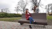 Female teenagers listening to music on smartphone at the bench in an autumn city park Stock Footage