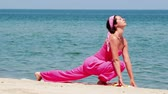 mind body soul : Beautiful young woman is doing exercises yoga on the seashore, Video clip Stock Footage