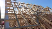 переделывать : New residential construction home framing against a blue sky