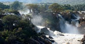 Намибия : famous Epupa Falls on the Kunene River in Northern Namibia and Southern Angola border. Sunrise sunlight in water mist. This is africa. Beautiful landscape. Стоковые видеозаписи