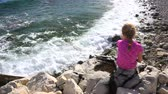 четыре человека : Little girl on beach, facing away from viewer, sitting on rocks, playing and watching he waves