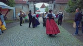 étnico : Slovneska Bistrica, Slovenia - Sept. 7 2019: Folklore dancers wearing national costumes perform traditional Slovene folk dance on street accompanied with accordeon player
