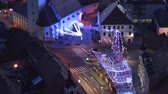 рынок : Slovenska Bistrica, Slovenia - Dec 25 2019: Aerial view of Christmas fair on main square in Slovenska Bistrica, a small medieval town in Slovenia, cars pass by on main street