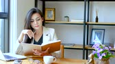 spuštění : 4K footage, beautiful Asian business woman sitting in front of computer laptop , reading and flip over note book page with thinking face at workspace in the morning , business people lifestyle. Dostupné videozáznamy