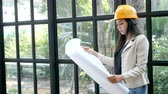 eletricista : young Asian female construction engineer in a yellow hard safety helmet hat holding architect blueprints in hand, reading and checking on blueprint