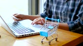 online banking , shopping concept. female hand holding a credit card and shopping online. shopping online with credit card at home lifestyle, shopping cart in foreground