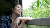 4K. asian woman travel by train looking out of a train window on railway train start at Bangkok go to Kanchanaburi in Thailand. enjoy transportation by vintage train