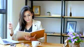 кафетерий : 4K footage, beautiful Asian business woman sitting in front of computer laptop , reading and flip over note book page with thinking face at workspace in the morning , business people lifestyle. Стоковые видеозаписи