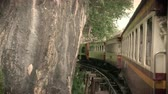 4K footage of an ancient train running on a sharp curved rail curving onto a bridge across the River Kwai, film color filter effect. popular attraction for foreign tourist in Thailand