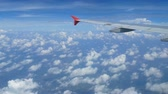 4K footage. traveling by air. aerial view through an airplane window. wing airplane and beautiful white clouds in blue sky for background Stock Footage