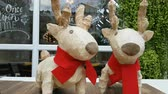 couple of reindeer sculpture with red scarf as decoration with commercial shop at background